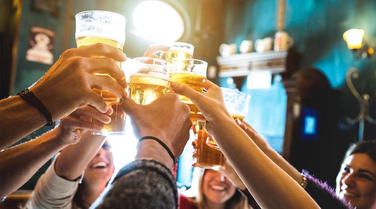 Gente brindando con cerveza en un bar