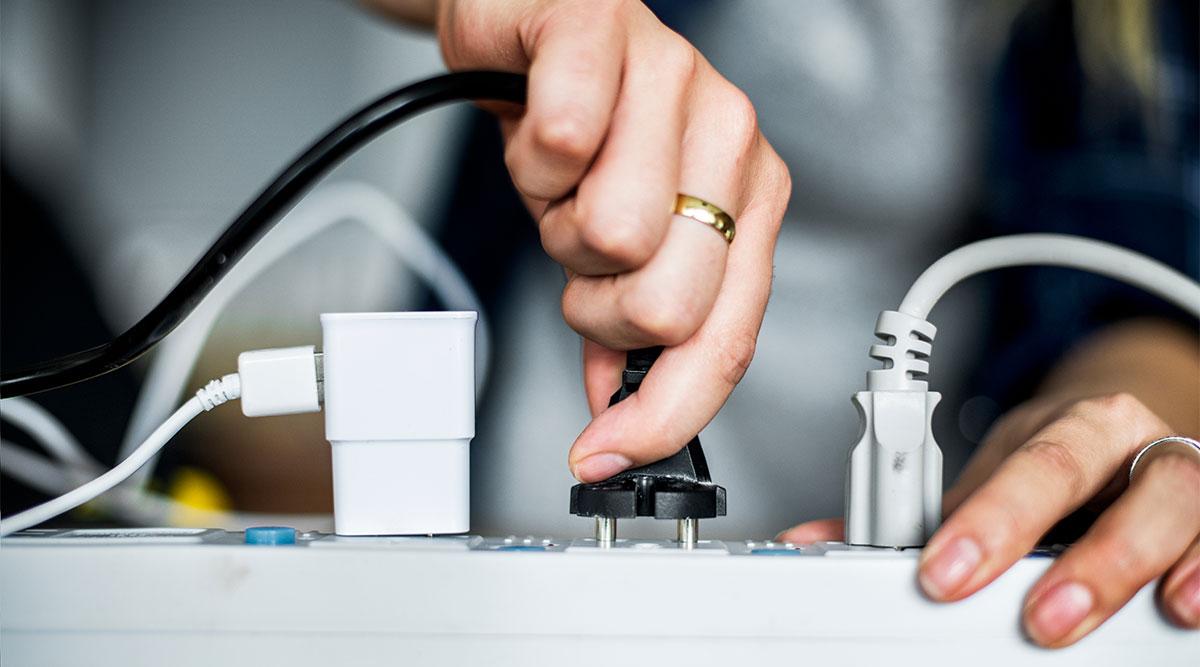 Persona conectando un enchufe, riesgo de electrocución ILT
